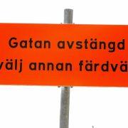 Orange vägskylt med svart text: Gatan avstängd. Välj annan väg.