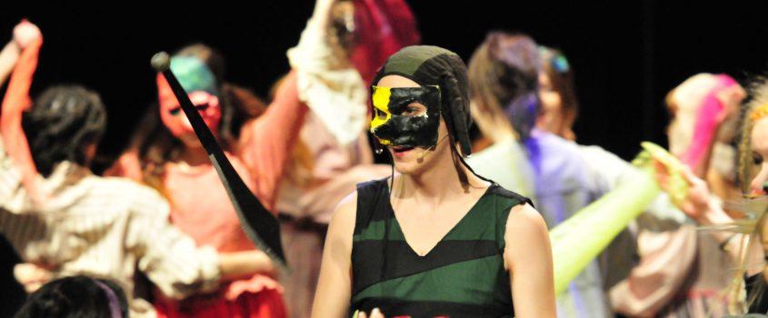 Teatersällskap som har på sig masker och dansar runt
