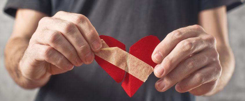 Händer som håller ett rött itudelat och ihoptejpat pappershjärta