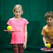 En flicka och en pojke som balanserar tennisboll på tennisracket