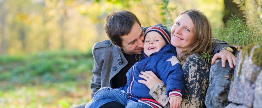 En familj, pappa, barn och mamma, sitter utomhus i naturen och har roligt tillsammans.