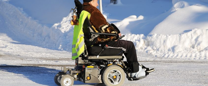 Man som färdas med hjälp av permobil på vinterväg