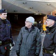 Två poliser står och samtalar med en medborgare vid järnvägstunneln
