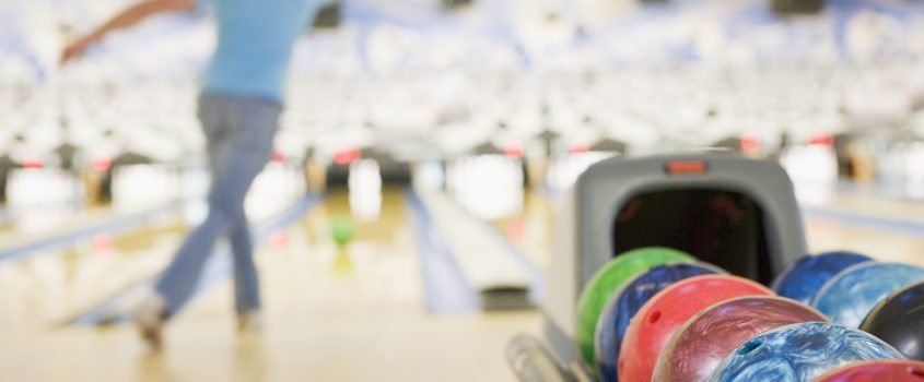 Bowlinghall med en person som kastar iväg ett bowlingklot