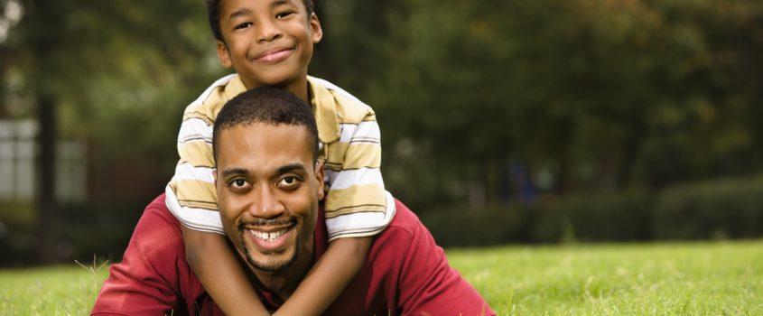 En pappa ligger i gräset och hans son klättrar på ryggen och kramar honom