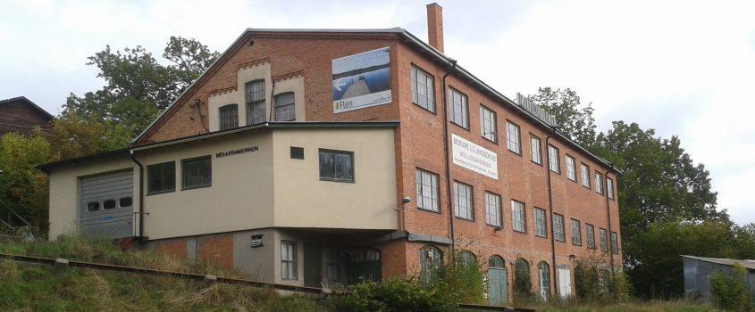 Äldre fabriksbyggnad i tre våningar med fasad av tegel och stora spröjsade fönster.
