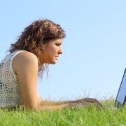 Ung tjej ligger i gräset och skriver på sin laptop