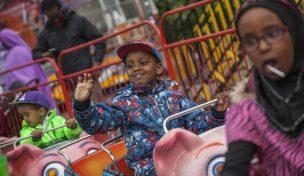Pojke som vinkar från en karuselll