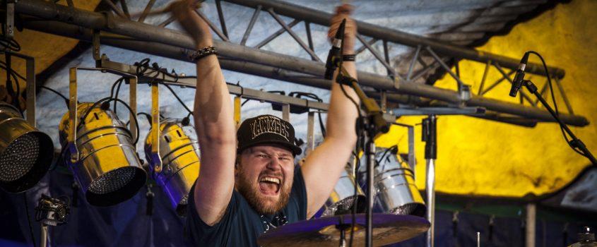 Trummis som höjer armarna över huvudet i en glad gest