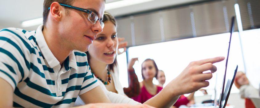 Studenter i ett klassrum som jobbar vid sina laptops