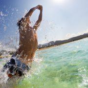 Ung kille som hoppar i vattnet, badar och har kul
