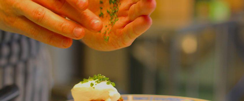 Två händer över tallrik med maträtt