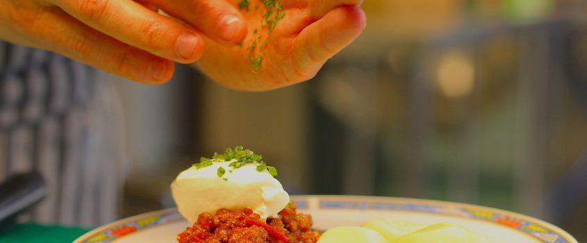 Händer som kryddar en maträtt