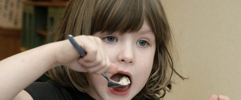 Flicka äter mat
