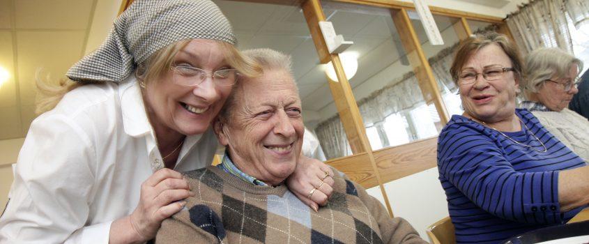 Måltidspersonal kramar om en senior herre vid matbordet