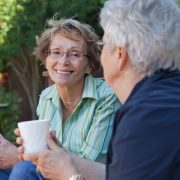 Två äldre kvinnor som dricker kaffe utomhus