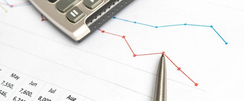 Närbild på ett papper med budgetsiffror, en penna och en miniräknare