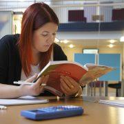 En student sitter vid ett skrivbord och läser i en bok.