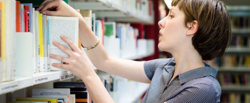Kvinna på bibliotek sorterar in böcker i bokhyllor