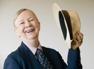 Dramatic senior woman in a man's suit holding a straw hat