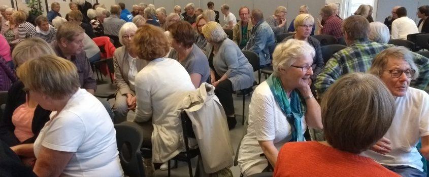 Ett femtiotal personer i övre medelåldern som samtalar runt olika bord. Plats: Skjortan i Flen