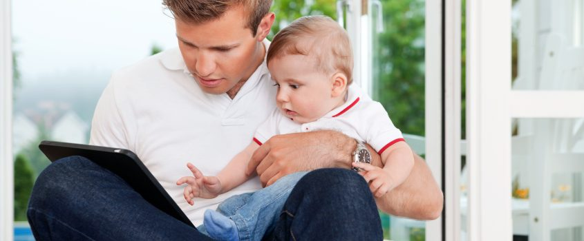 Man som använder en surfplatta samtidigt som han har ett barn i sitt knä