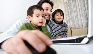 Pappa framför dator med två barn på vardera sida