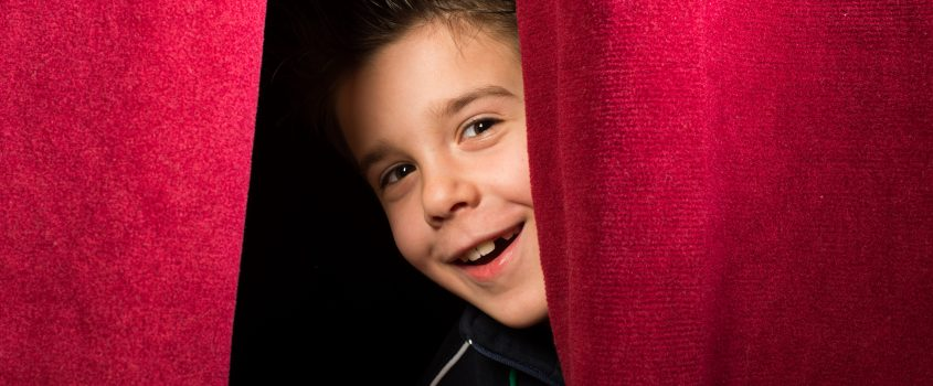 Pojke tittar fram bakom röd gardin