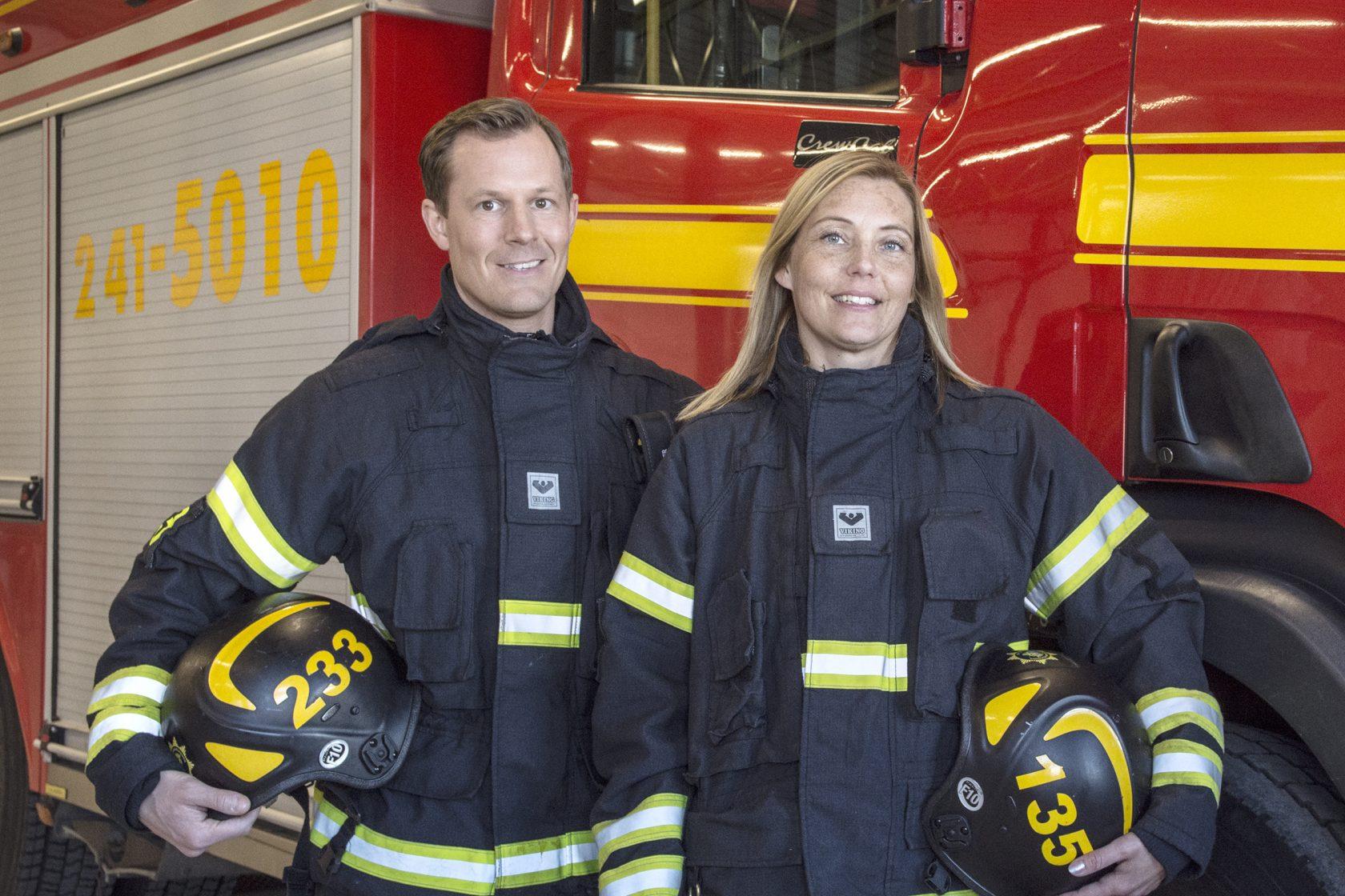 Två brandmän framför en brandbil