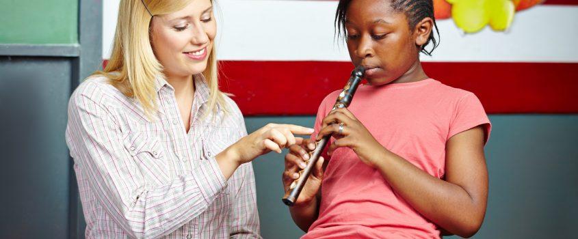 En lärare visar en elev hur eleven ska spela på en flöjt