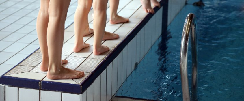 Ben och fötter på kanten av simbassäng