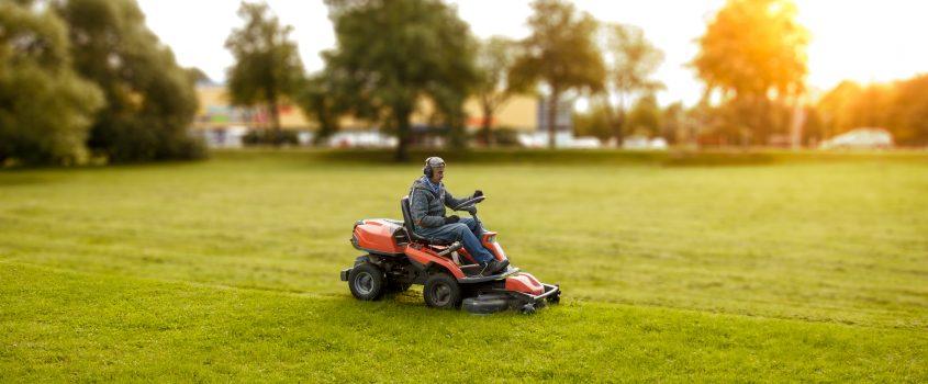 Person på en traktorgräsklippare en solig kväll