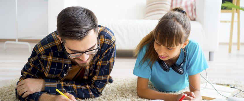 Pappa med tonårsdotter läser läxor tillsammans