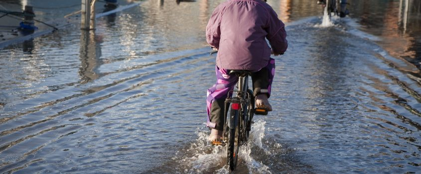 Pojke som cyklar genom en vattenansamling på översvämmad väg