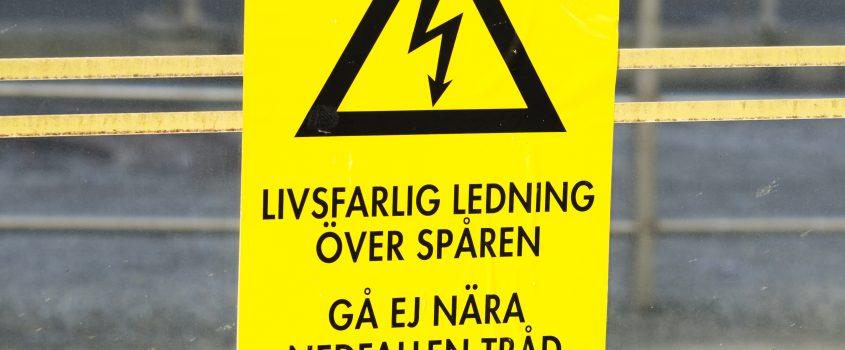Skylt med text: Livsfarlig ledning - Gå ej nära nedfallen tråd
