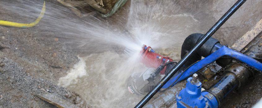 Vatten som sprutar ur ett rör i marken