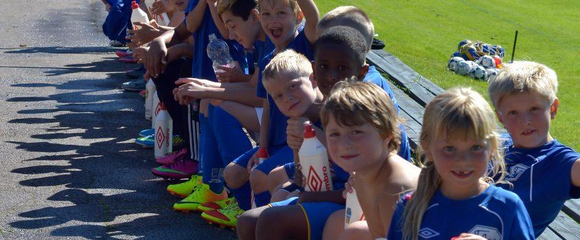 En grupp barn sitter på en bänk och vinkar, skrattar och gör segertecken iklädda fotbollskläder & skor