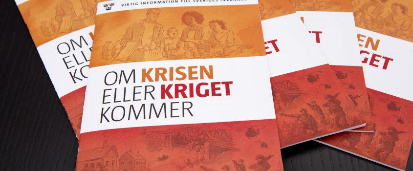Flera exemplar av broschyren När krisen eller kriget kommer som ligger på en mörk bordsskiva