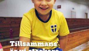 En leende pojke i gymnastikkläder tittar in i kameran.