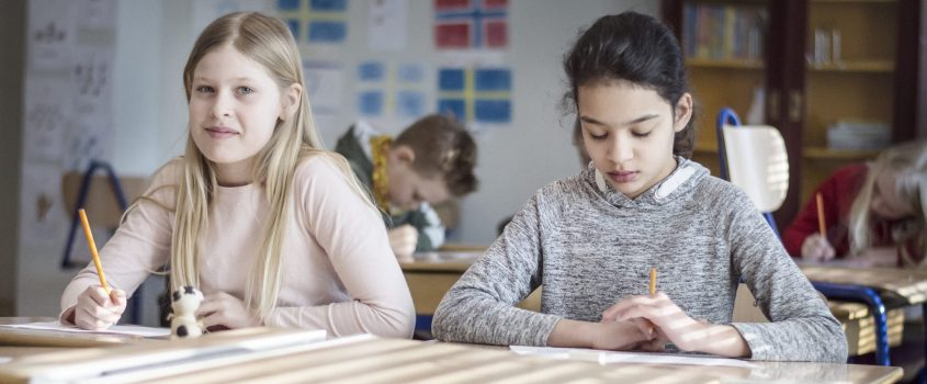 Elever vid bänkar i klassrummet.