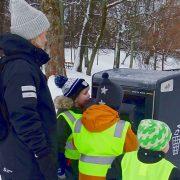 En vuxen och tre barn slänger skräp i en sopkorg. Det är vinter.