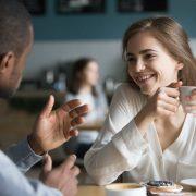 En kvinna och en man diskuterar något över en kopp kaffe