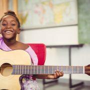 Flicka som spelar på en gitarr i ett klassrum