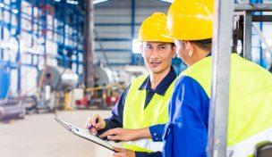 ingenjörer i gula skyddshjälmar samtlalar inuti en industribyggnad