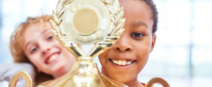 En pojke och flicka lyfter stolt fram en vinnarpokal. Pojken håller i pokalen och flickan skrattar/ler.