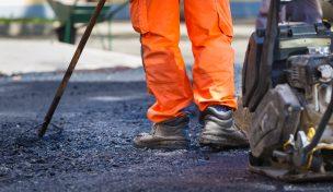 Person i orangea arbetskläder genomför asfaltering