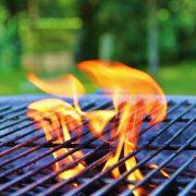 Bild på låga ur en grill som står utomhus
