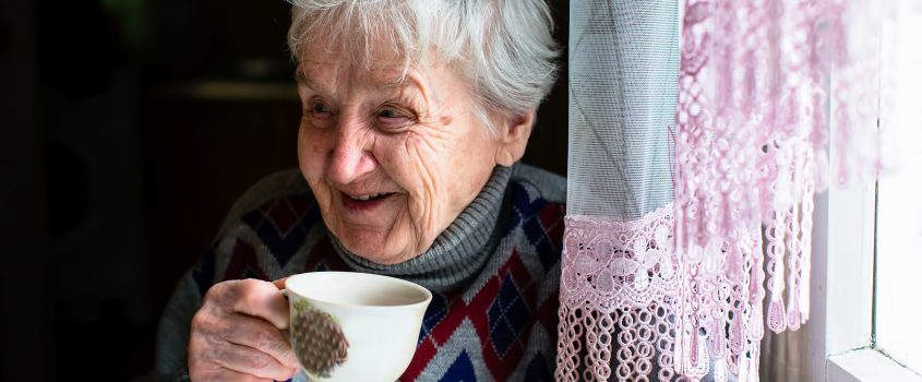 Äldre dam som sitter vid ett fönster och ler och dricker kaffe
