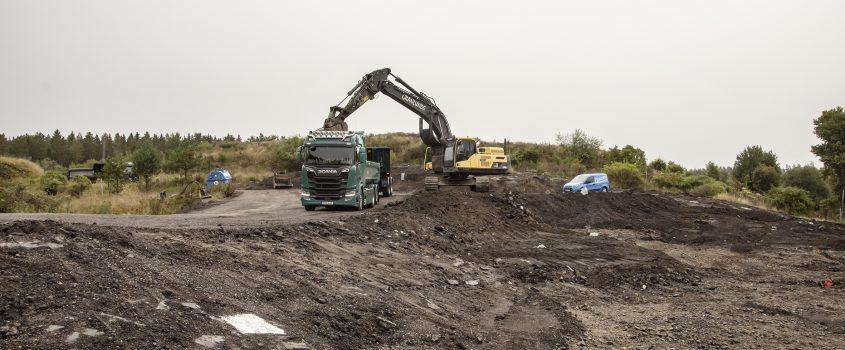 Grävskopa lastar avfaltsavfall på ett lastbilsflak
