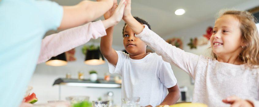 """Barn i skolmatsal sittandes vid bord med lunchtallrik framför sig. De ger varandra en """"high five"""""""